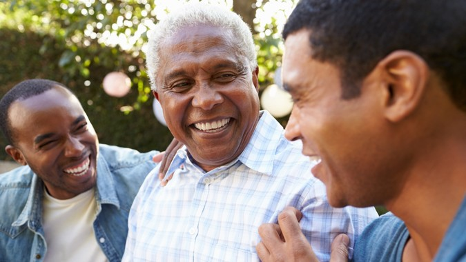 Senior man talking with his adult sons in garden, close up.