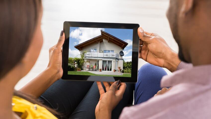 Couple Looking At House On Digital Tablet.