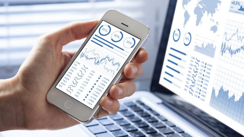 stocks on a smartphone and laptop screen