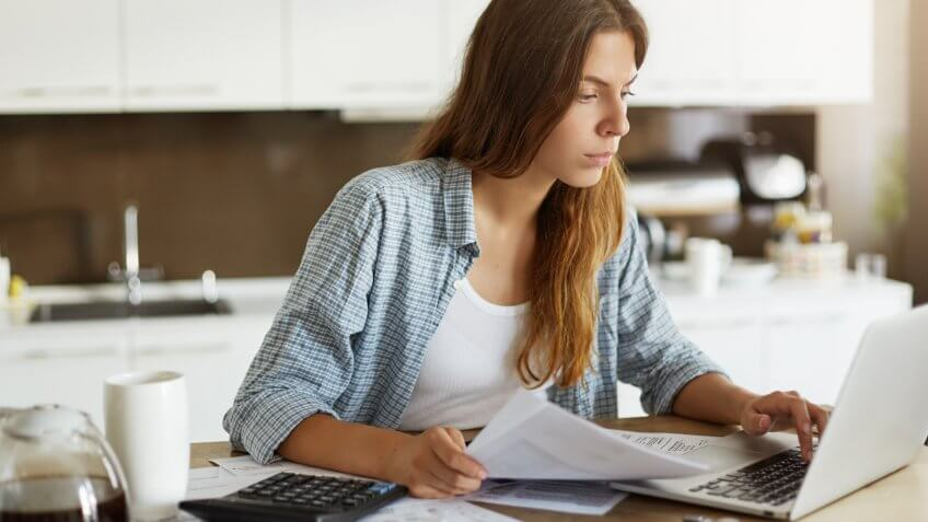 woman reviewing billing statements and looking at laptop