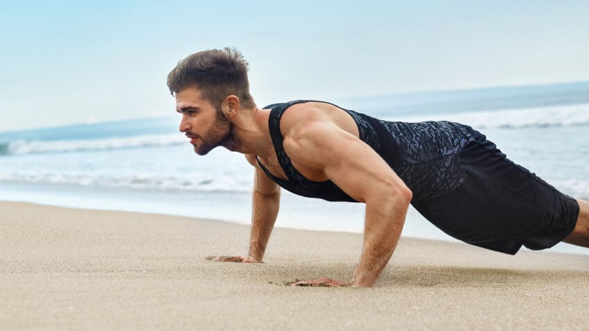 man doing a push up on the beach