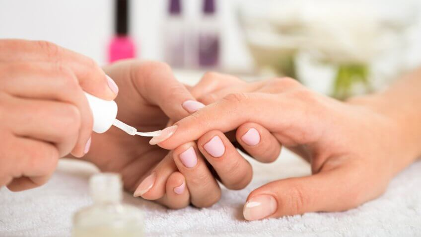 manicurist doing manicure client painting nails with transparent nail polish in salon on white towel.