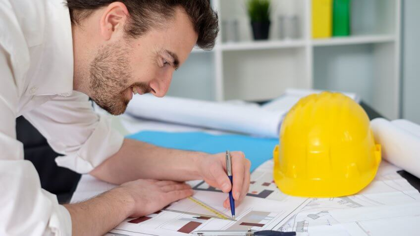 construction man drawing on blueprints with a yellow hard hat