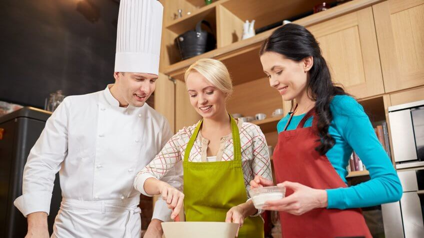 professional chef teaching two women how to cook