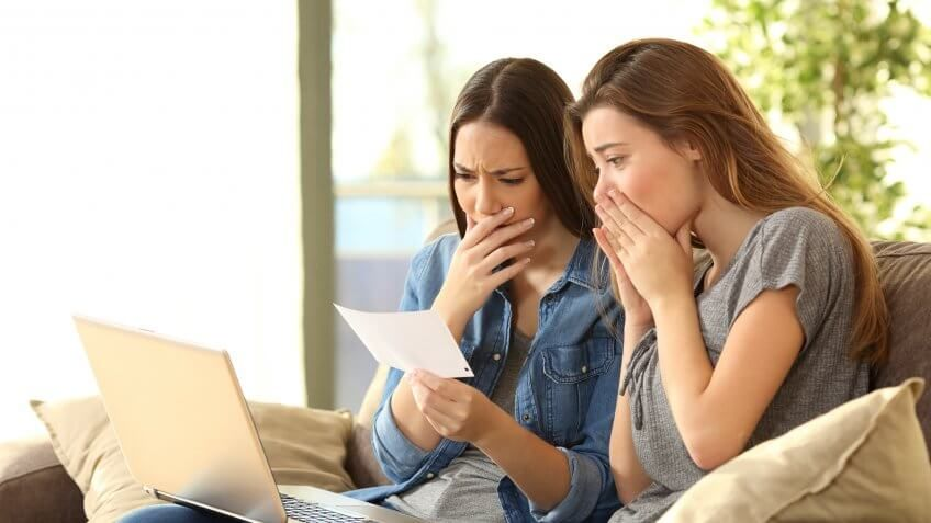 two women looking upset at a piece of paper