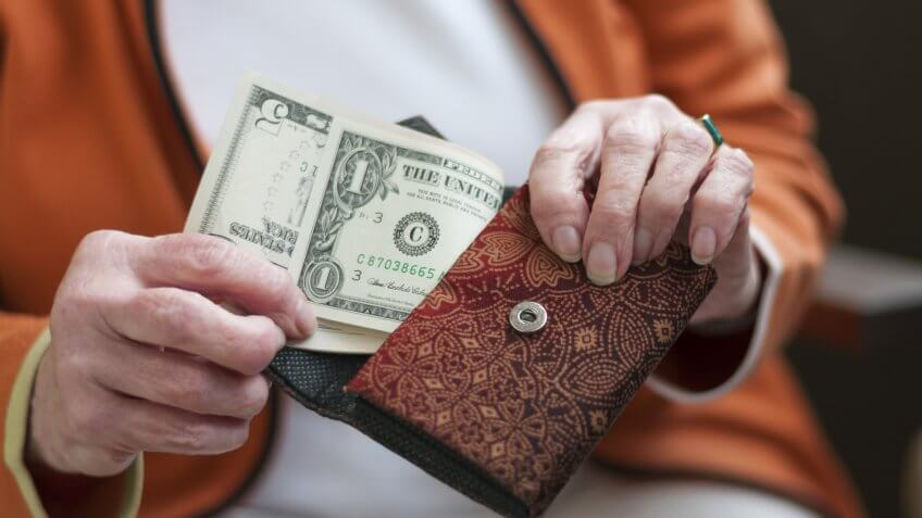 elderly older woman pulling money cash out of her wallet