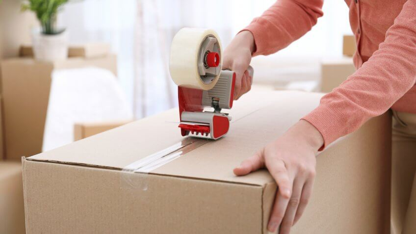 woman using packing tape on a moving box