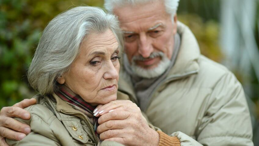 senior old couple holding each other looking sad