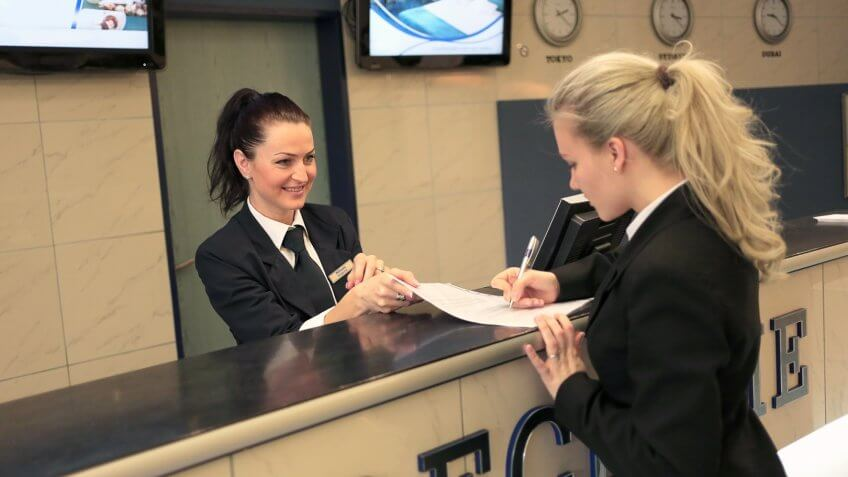 person signing a paper at a hotel concierge