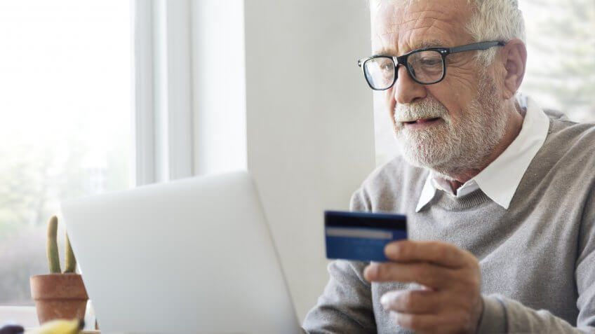old senior man holding credit card typing on laptop