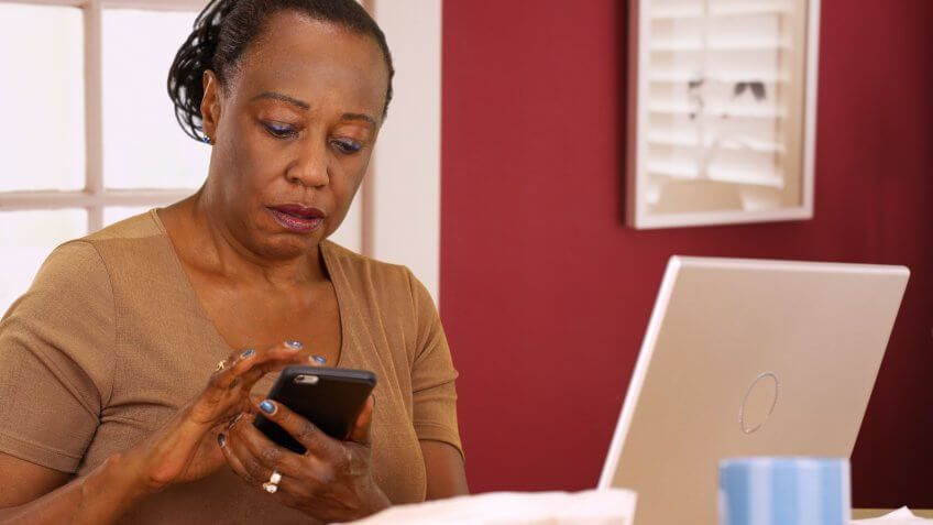 woman on her smartphone next to her laptop