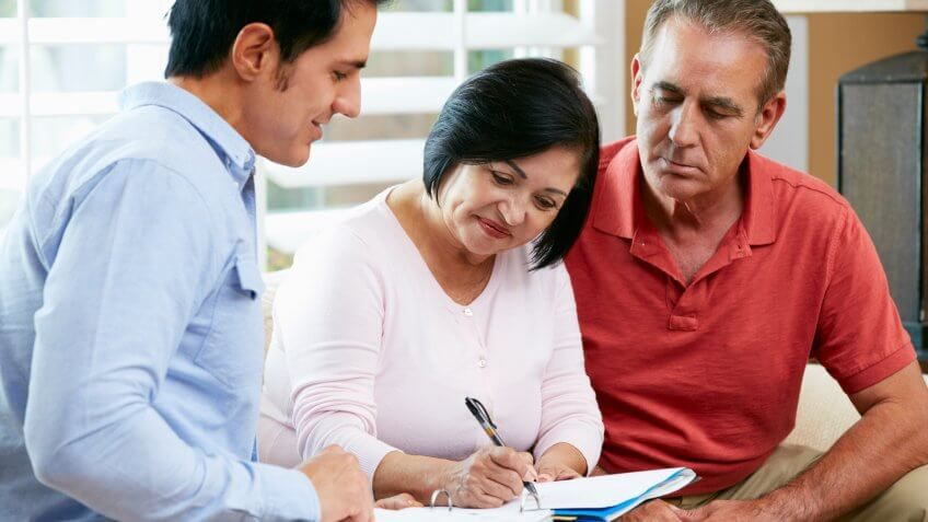 older couple filling out form with an adviser