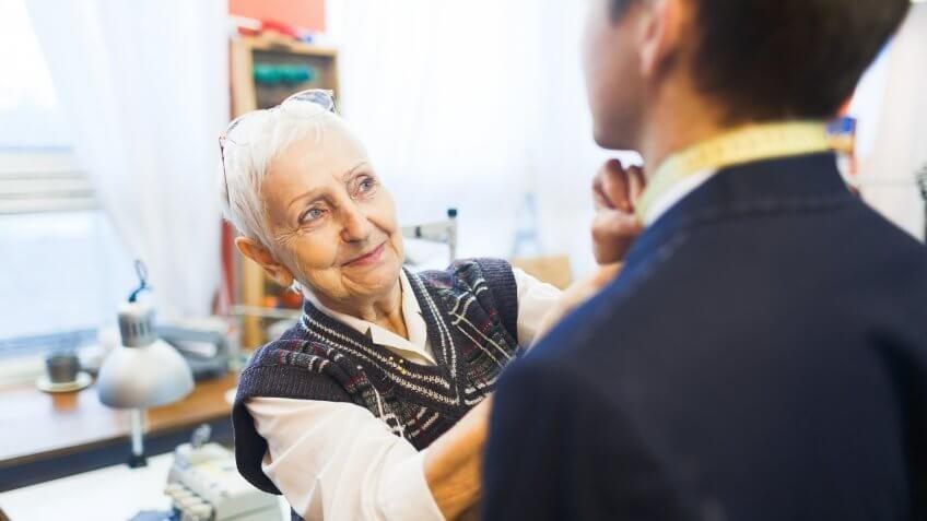 older senior woman tying mans tie