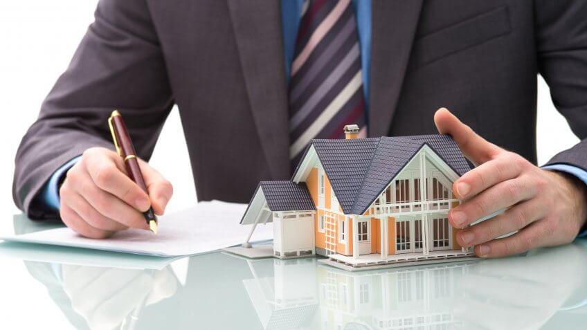 man holding toy house signing documents