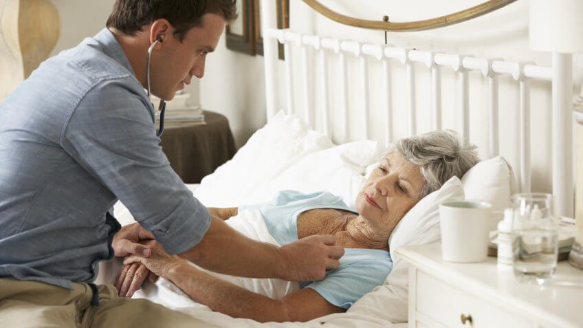 doctor with stethoscope to old senior retired woman in her home bed