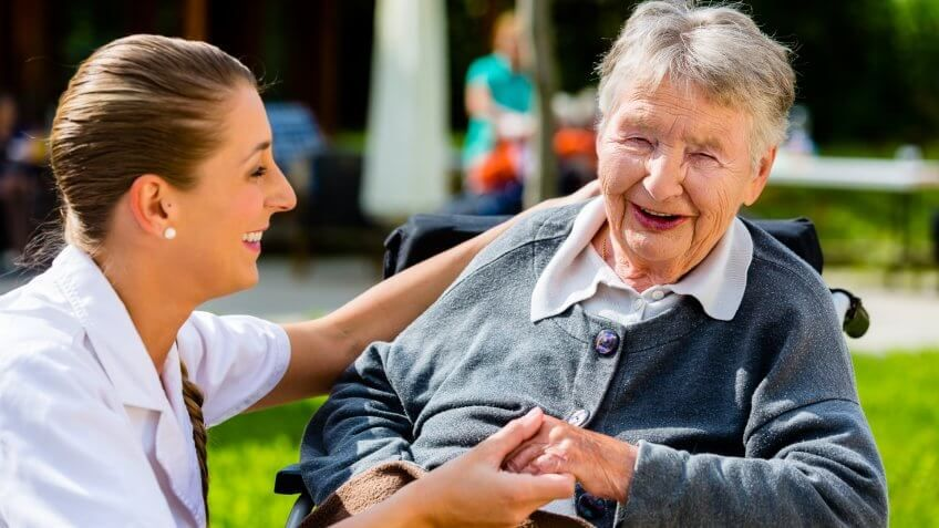 senior care young woman talking to a retired old woman