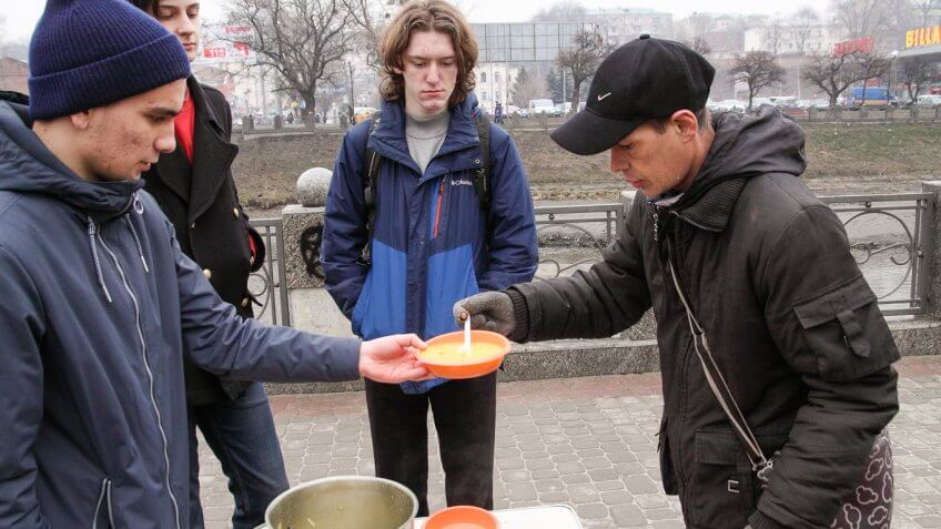 man giving soup to another man outside soup kitchen
