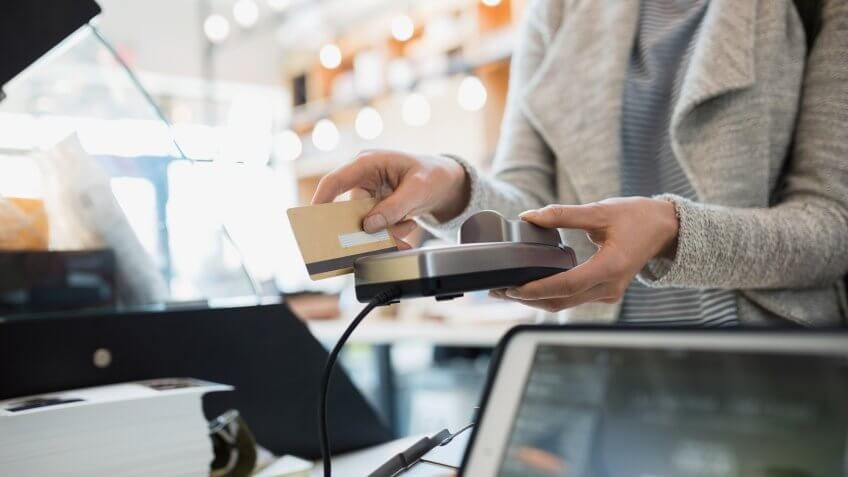 Customer paying at credit card reader in market.