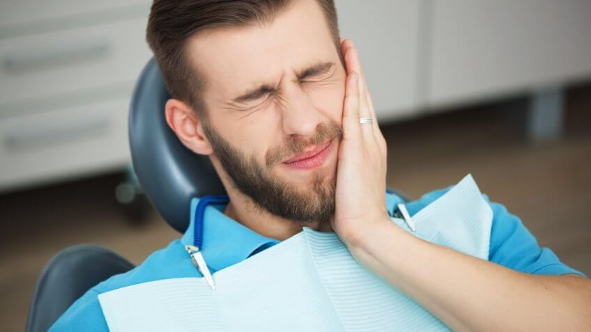 young man with tooth pain while sitting in a dentist's chair