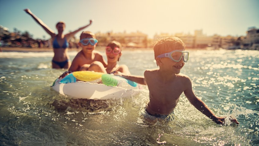 Little boy aged 7 having fun at sea with his family.