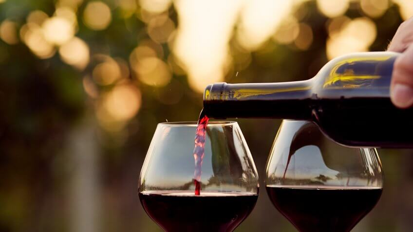 Pouring red wine into glasses in the vineyard