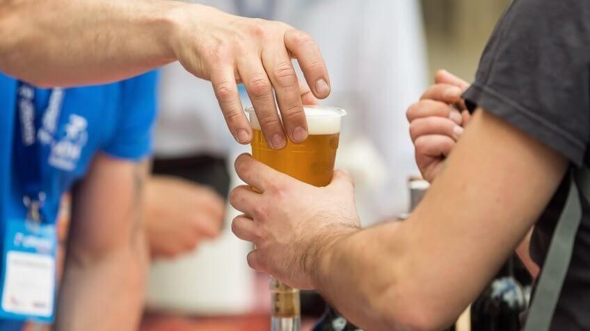 worker handing a customer beer