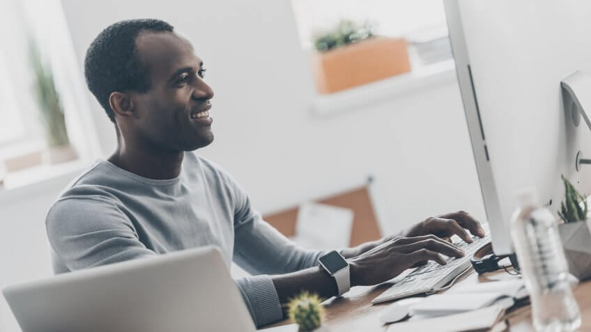 man smiling while typing on his computer