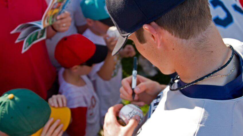 baseball player autographing signing a ball