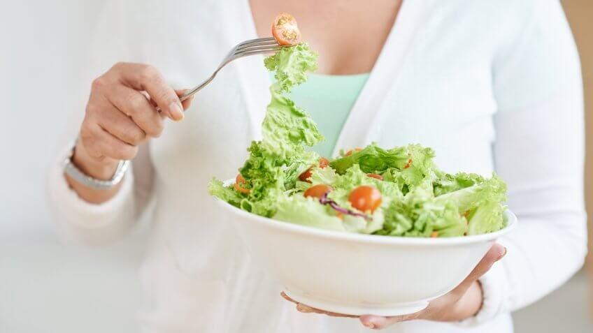 woman eating a bowl of salad