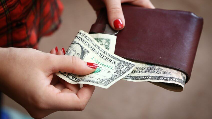 Woman with one dollar bill in wallet
