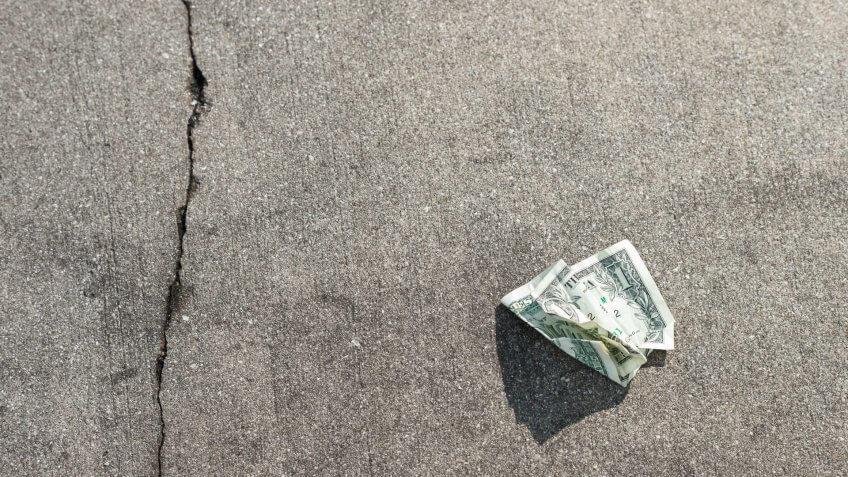 US Dollar Bill in on Concrete Sidewalk.
