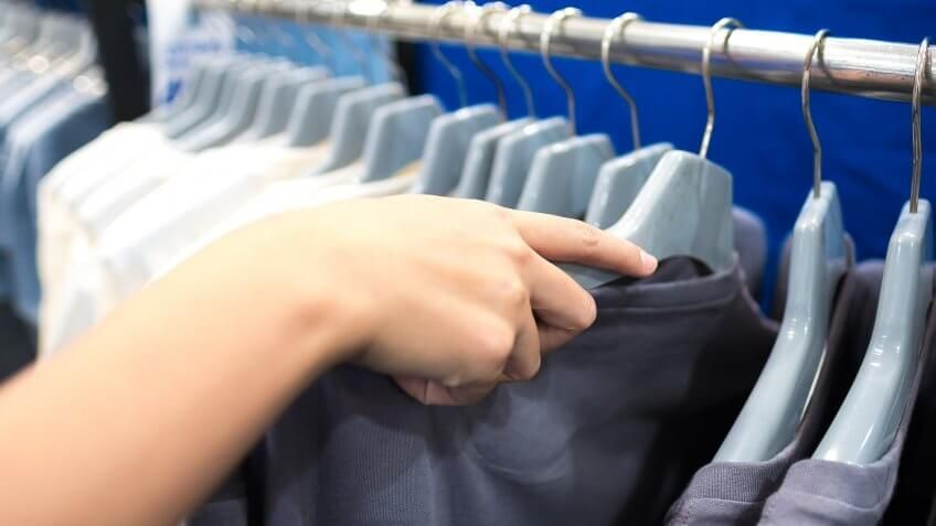 person pulling a tshirt out from a rack