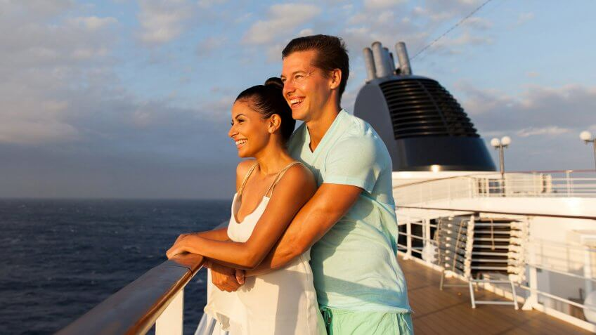 cheerful young couple looking at sunrise on cruise ship.