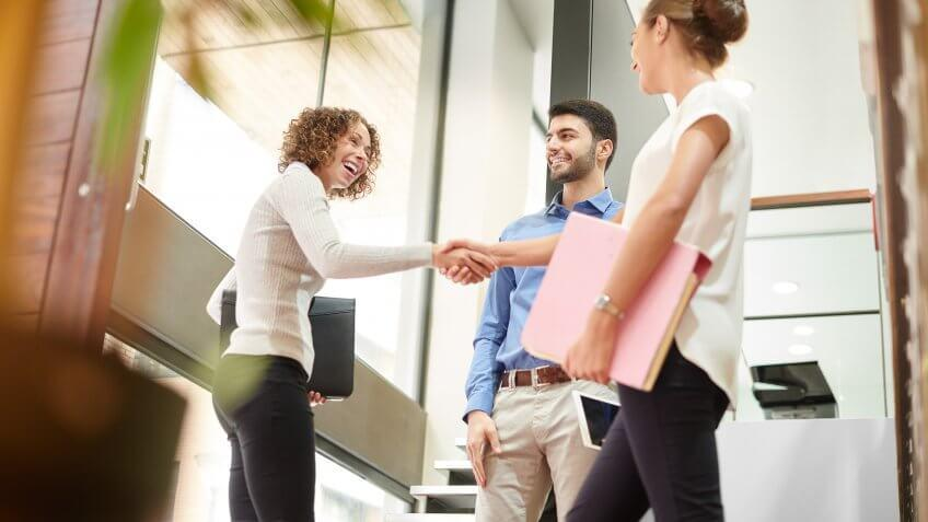 three business associates say goodbye or hello at the door of a modern office.