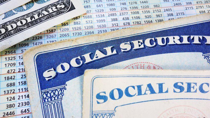 Social Security cards with cash and benefit amount numbers.