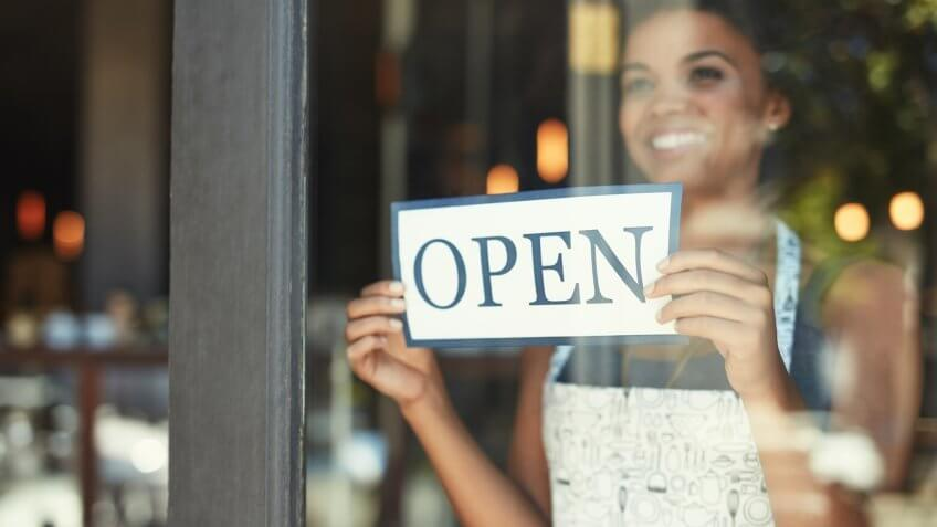 Cropped shot of a young woman hanging up an open sign on the window of her cafe.