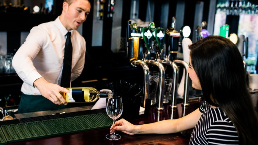 Barman serving a glass of wine in a bar.