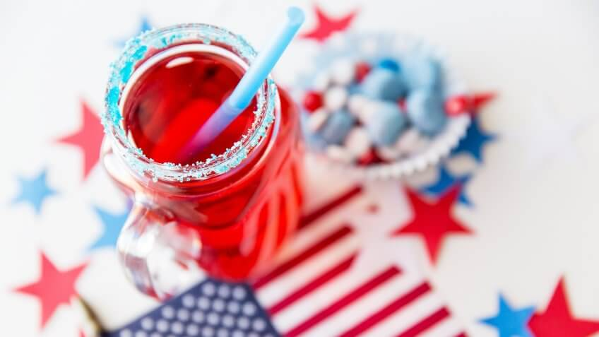 6 Red, White and Blue Batch Cocktails for Under $12, american independence day, celebration, flag and candies at 4th july party, patriotism and holidays concept - close up of juice glass