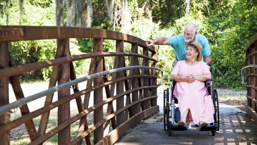 senior man walking wife in wheelchair