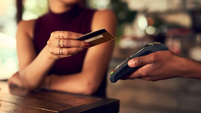 Closeup shot of a woman paying using NFC technology in a cafe.