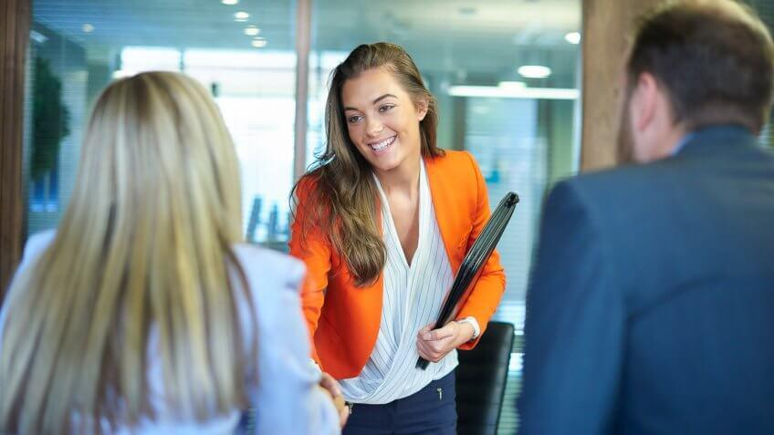 a young graduate walks into an interview room full of confidence and positivity energy .