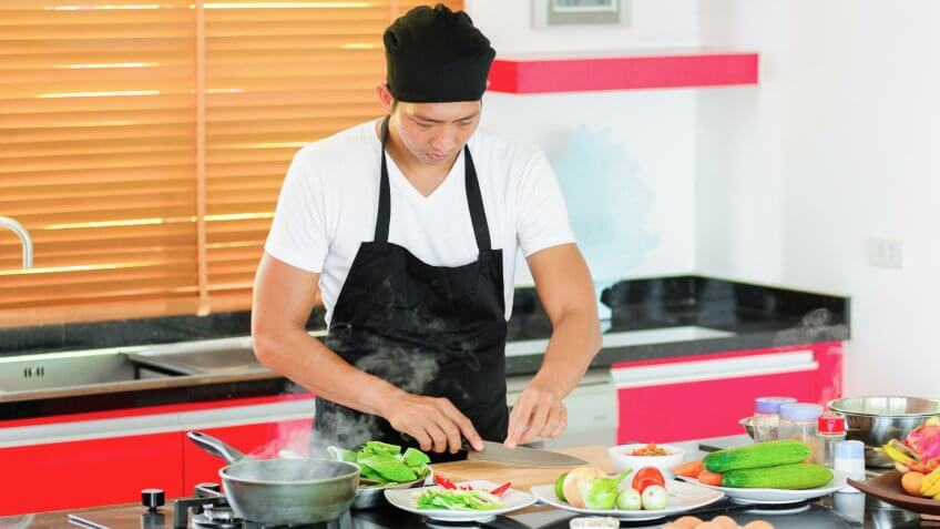 22 Industries That Pay Less (and More) Than They Did 10 Years Ag, Private Thai chef cooking in a modern style home kitchen. Making