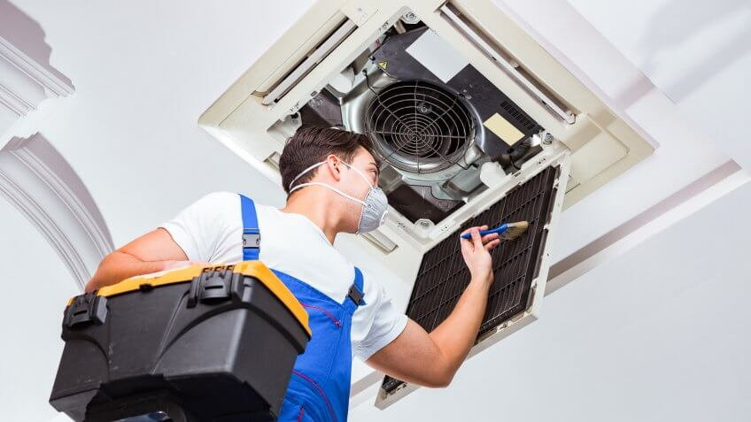 22 Industries That Pay Less (and More) Than They Did 10 Years Ag, Worker repairing ceiling air conditioning unit