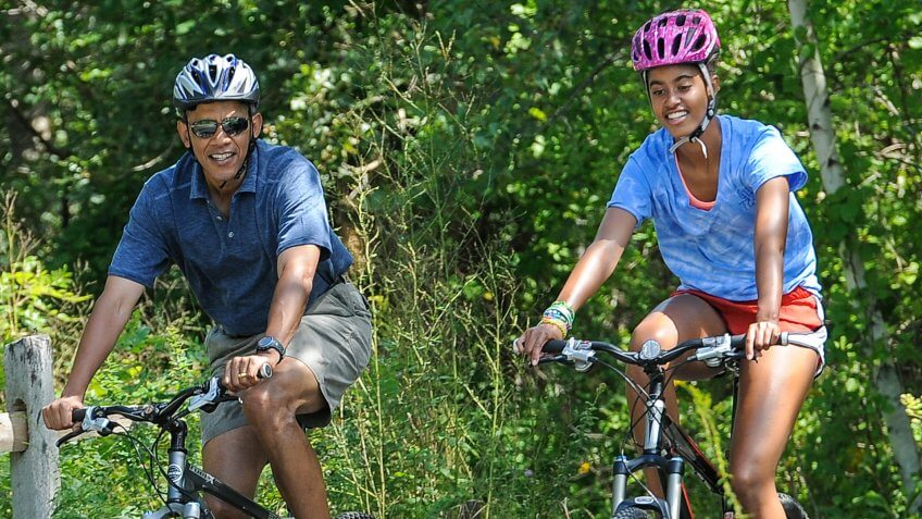 Barack Obama riding a bike with daughter
