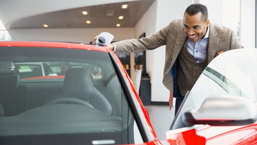 Man looking inside car in car dealership showroom.
