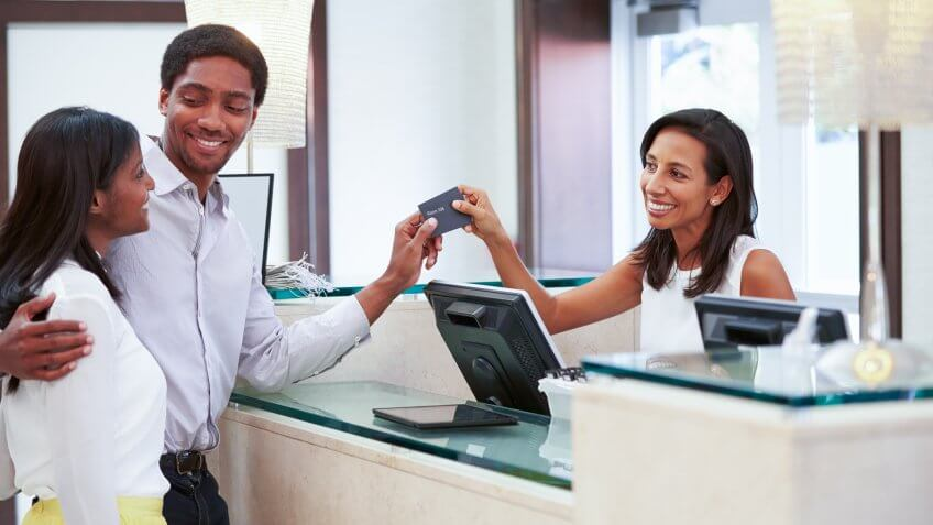 Couple Checking In At Hotel Reception, Free Hotel Upgrades That You're Missing Out On