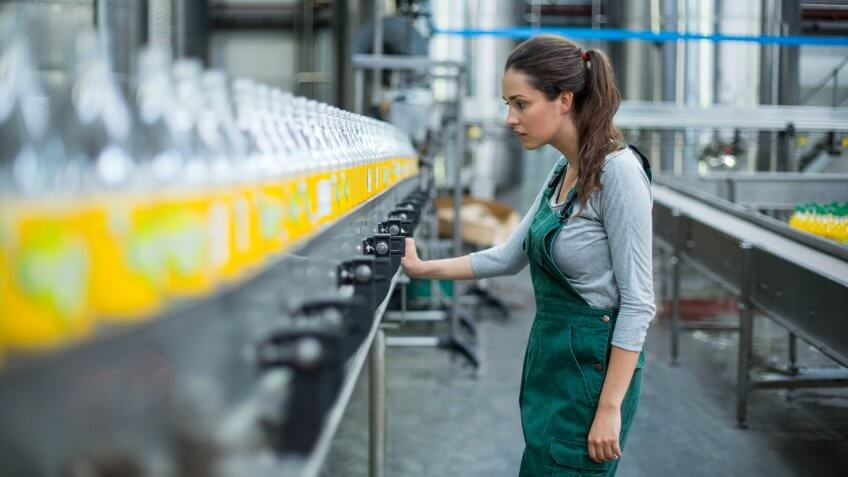 22 Industries That Pay Less (and More) Than They Did 10 Years Ag, Female factory worker inspecting production line at drinks produ