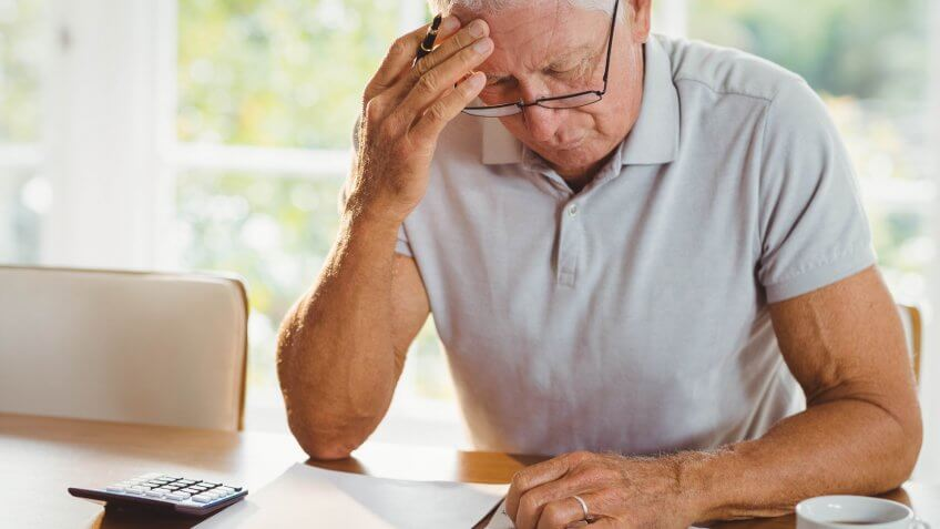 Secrets About Retiring That No One Wants to Talk About, Worried senior man with tax documents at home
