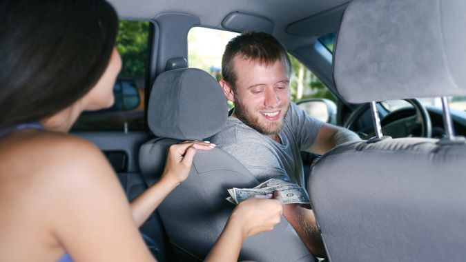 Female client giving money to taxi driver