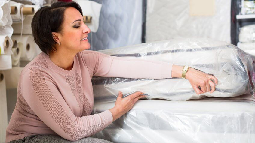 Positive female customer posing with mattress specimen inside te, The Best and Worst Things to Buy in August 2017